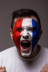 Portrait Euphoric scream of France football fan in win game of France national  team  on grey background. European  football fans concept.