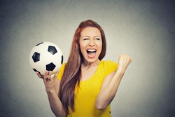 Portrait excited woman screaming celebrating team success holding football