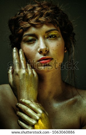 portrait extravagant and extreme gold makeup on cute girl face #1063060886