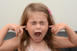 Portrait face of a young girl (age 05) with closed eyes and covering ears screaming very loudly. Concept photo of children stress and child anxiety.Real people. Copy space
