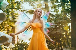 Portrait fantasy woman blonde forest fairy. Elf girl fashion model in bright yellow dress, butterfly wings.  walks in summer nature. Green spring tree, wood, sun light magic radiance. Long hair.