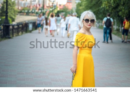 Portrait. fashionable lifestyle. to close. adult blond woman with blond hair in sunglasses walks at street, stylish casual outfit