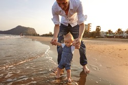 Portrait father with toddler son playing on the beach