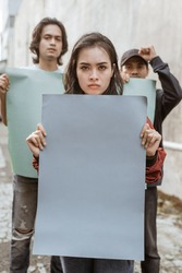 Portrait female students demonstrating with their friends holding blank paper