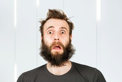 Portrait freak bearded shaggy surprised man with long hair before haircut in barbershop with open mouth and wide eyes.