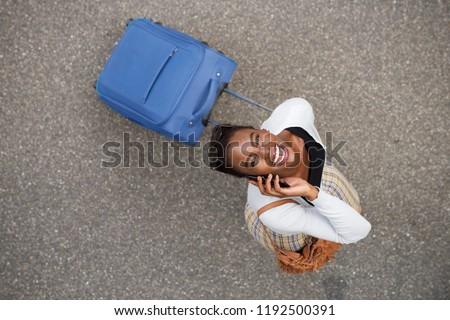 Portrait from above of happy african american woman walking with suitcase and mobile phone #1192500391