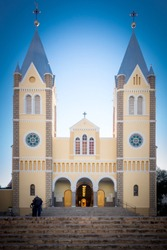 Portrait Front View - Saint Mary's Peach Coloured/Colored Twin Tower Cathedral With Open Door, Against A Clear Blue Namibian Sky, With Brown Stairs - Roman Catholic Church City Center Windhoek Namibia