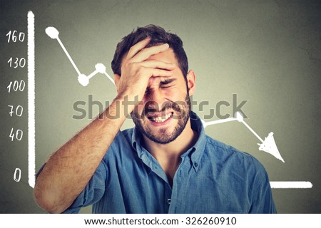 Portrait frustrated stressed young man desperate with financial market chart graphic going down on grey office wall background. Poor economy financial crisis concept. Face expression, emotion