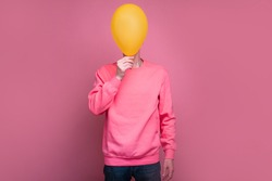 Portrait full lenght of man in pink sweater cover face behind yellow balloon. Tall incognito male person stand alone. Isolated over pink background