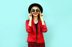 Portrait funny smiling woman showing mustache her hair in black round hat, red jacket on blue background