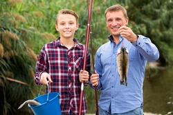 Portrait glad man with teenager boy standing together and showing catch fish outdoors