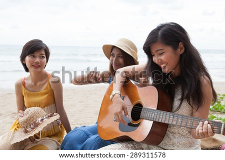portrait group of young asian woman playing guitar in sea beach picnic party at sea side with happiness face emotion