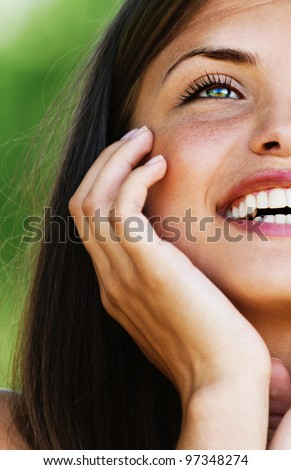 Portrait half face of laughing young woman with bared shoulders.