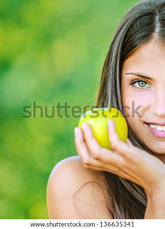 Portrait half of face young beautiful woman with bare shoulders holding an apple and smiling, on green background summer nature.