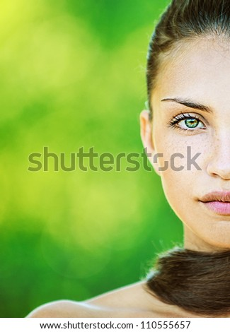 Portrait half of face young beautiful woman with bare shoulders, on green background summer nature.