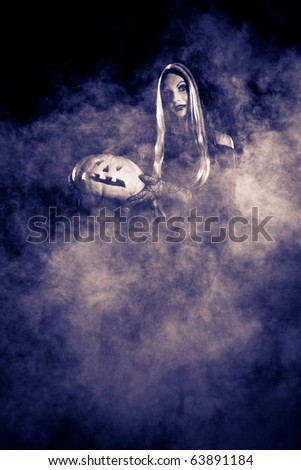 Portrait Halloween witch with a pumpkin. Smoke background