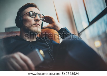 Portrait handsome bearded man wearing glasses,headphones listening to music at modern home.Guy sitting in vintage chair,holding smartphone and relaxing.Panoramic windows background.Blurred background