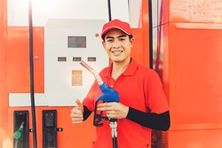 Portrait handsome male asian worker wearing a red uniform stands with a gas nozzle serving customers as they refuel at a quality gas station : Honorable service career in a gas station concept