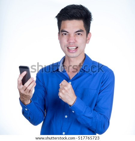 Portrait handsome young asian man wearing a blue shirt successful businessman celebrating his victory  with smartphone on hand young isolated on white background. Asia man people. #517765723