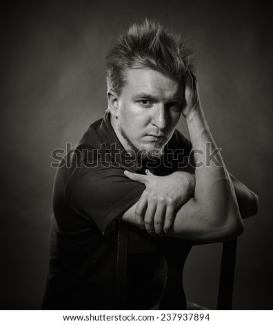 Portrait, handsome young man sits in the studio - black and white image, dark background