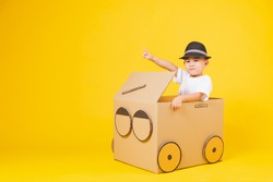 Portrait happy Asian cute little children boy smile so happy wearing white T-shirt driving car creative by cardboard and pointing finger, studio shot on yellow background with copy space