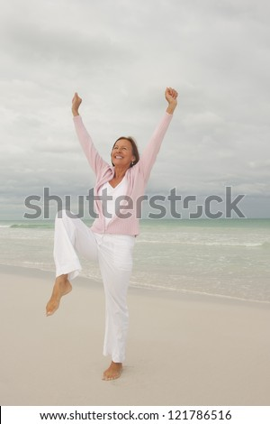 Portrait Happy beautiful middle aged woman smiling joyful and cheerful arms up at beach holiday and active retirement, isolated with ocean and overcast sky as blurred background and copy space.