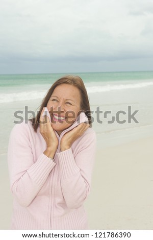 Portrait Happy beautiful middle aged woman smiling joyful at beach holiday and active retirement, isolated with ocean and overcast sky as blurred background and copy space.