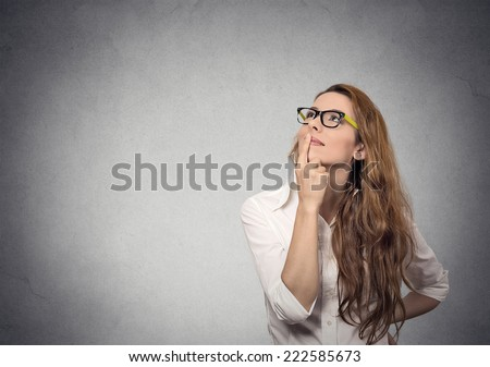 Portrait happy beautiful woman thinking looking up isolated grey wall background with copy space. Human face expressions, emotions, feelings, body language, perception