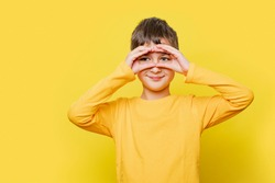 portrait happy child boy looking, observing, keeping an eye on an object in front, or watching out for something. spy boy on colorful yellow background - image