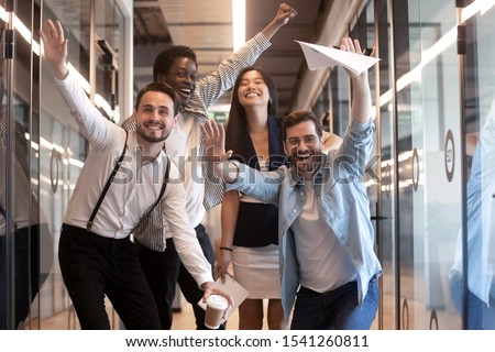 Portrait happy diverse employees celebrating business victory, excited team having fun at corporate party, smiling and laughing colleagues looking at camera, standing in modern office hallway