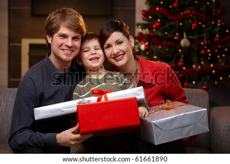 Portrait happy family at christmas, holding presents, smiling.?