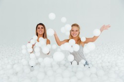 Portrait Happy Girlfriends stand surrounded by white plastic balls in the dry pool. Spend fun time. Adult childhood at Playground with pit-ball. Throw balls in the camera frame.