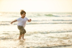 Portrait Happy little Asian boy running and playing with smiling and laughing on tropical beach at sunset. Portrait of Adorable young child kids having fun in summer holiday vacation travel.
