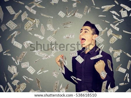 Portrait happy man exults pumping fists ecstatic celebrates success under money rain falling down dollar banknotes isolated on gray wall background #538618510