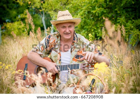 Portrait happy mature american man with guitar in casual style on outdoors in field #667208908
