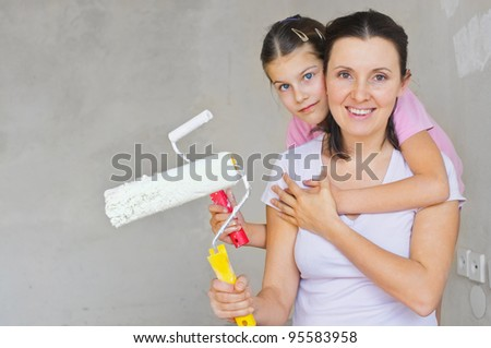 Portrait happy mother and douther with roller for painting a wall