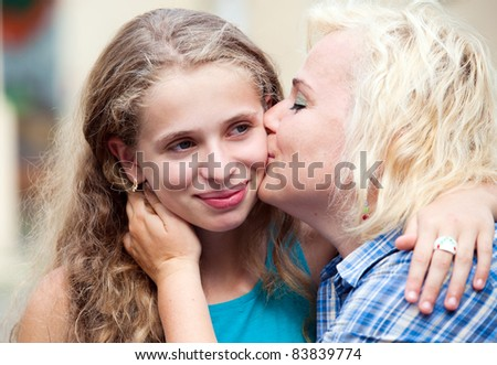 Portrait happy mother kissing her daughter