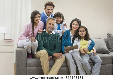 Portrait happy multi generation family using digital tablet sitting on sofa