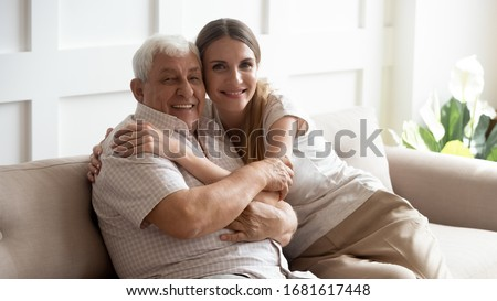 Portrait happy older father and adult daughter hugging, looking at camera, posing for photo, beautiful young woman with smiling mature dad or grandfather sitting on cozy sofa at home, two generations