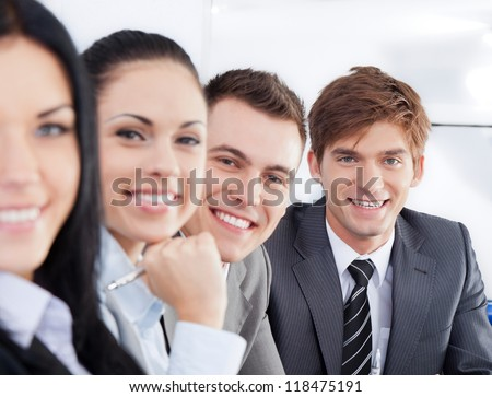 Portrait happy smile business people group in a row, looking at camera, businesspeople team sitting at desk in office