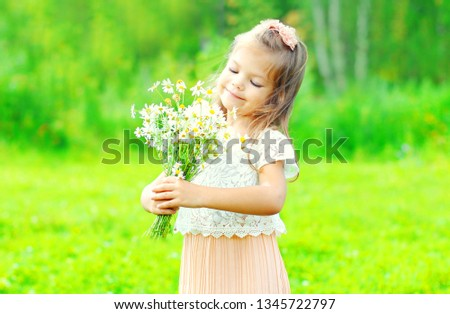 Portrait happy smiling little girl child holding bouquet flowers in her hands in spring day #1345722797