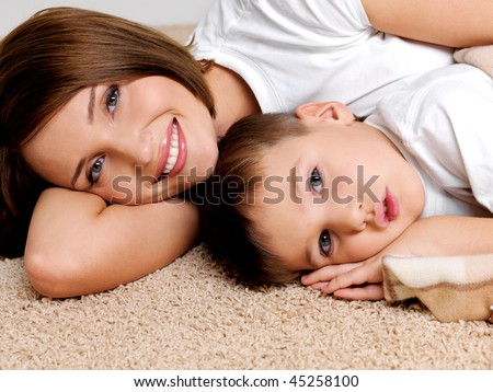 Portrait happy smiling  mother and the child lying on a floor in the apartment