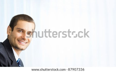 Portrait happy smiling successful business man at office. You can use right part for slogan, big text or banner.
