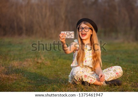 Portrait happy summer mood of joyful young girl in glasses, braces and black hat making a selfie on her smartphone and having fun in park. positivity, joy, happiness, smiling, healthcare #1375461947