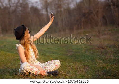 Portrait happy summer mood of joyful young girl in glasses, braces and black hat making a selfie on her smartphone and having fun in park. positivity, joy, happiness, smiling, healthcare #1375462085