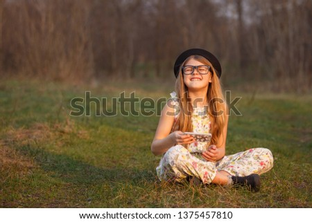 Portrait happy summer mood of joyful young girl in glasses, braces and black hat with smartphone having fun in park. positivity, joy, happiness, smiling, healthcare #1375457810