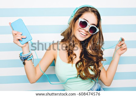Portrait happy summer mood of joyful young woman with long curly hair, in sunglasses, heels having fun on striped background.Blue colors, expressing positivity, music, joy, happiness, dancing, smiling