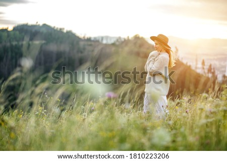 Portrait happy woman enjoying sunset stay on the green grass on the forest peak of mountain. Fresh air, Travel, Summer, Fall, Holidays, Journey, Trip, Lifestyle.
