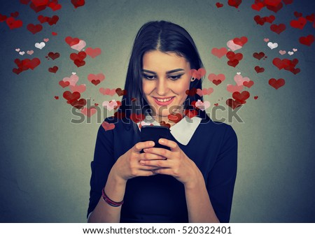 Portrait happy woman sending love sms text message on mobile phone with red hearts flying away from screen isolated on gray wall background. Human emotions feelings