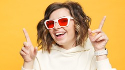 Portrait Happy Woman Smiling Dancing to Music Rhythmically to Beat Moving her Hands in Yellow Sweater Yellow Background in Sunglasses. Monotone. Positive Emotions of People. Freedom. Lifestyle